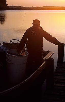 NC: Beaufort County, Pamlico Sound, Pungo River, River's mouth at Pimlico Sound, Fisherman Lee Morris launching his boat at sunrise. RELEASED [Ask for #224.285.]